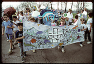 Kids and adults march in Earth Day parade with Let Oceans Live banner; Forest Park, St. Louis. Missouri