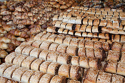 "Middle East, Israel, Jerusalem, rugelach and other fresh pastries on display for sale at Mahane Yehuda Market (also known as Machaneh Yehuda), often referred to as ""The Shuk"", is popular with locals and tourists alike, the market's more than 250 vendors sell fresh fruits and vegetables; baked goods; fish, meat and cheeses; nuts, seeds, and spices; wines and liquors; clothing and shoes; housewares, textiles, and even Judaica."