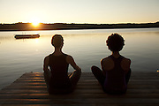 Two women meditating lakeside at sunrise.