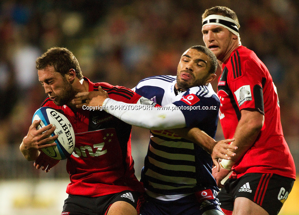 Tom Taylor for the Crusaders is tackled by Bryan Habana with Kieran Read behind the play. Super Rugby game between the Crusaders and the Stormers. Crusaders new Christchurch Stadium at Rugby League Park, Saturday 14 April 2012. Photo : Joseph Johnson / photosport.co.nz