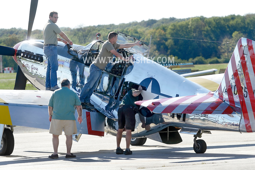 Montgomery, New York - Collings Foundation crew members work on of a P-51 Mustang fighter plane on the runway at Orange County Airport on Oct. 2, 2010.