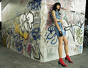 Young woman leaning against wall with graffiti.