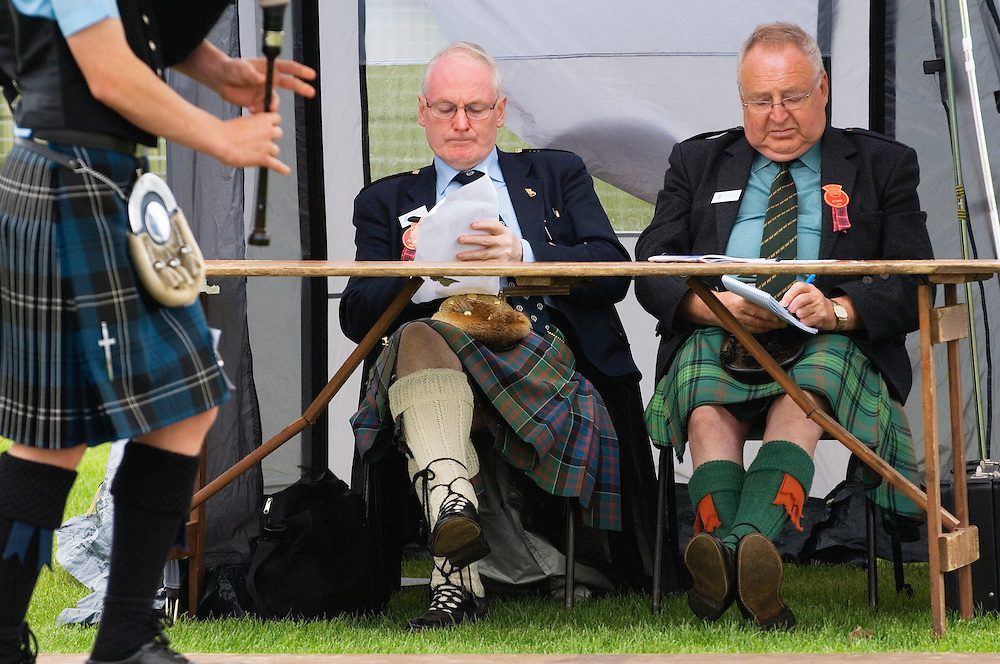 Bagpipe player and piping contest judges at the prestigious annual Cowal Highland Gathering at Dunoon, Strathclyde, Scotland.
