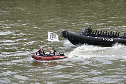 © Licensed to London News Pictures. 15/06/2016. London, UK. A police river boat passes some EU remain campaigners as a flotilla of remain and leave referendum boats converge on the Thames near Parliament. Photo credit: Peter Macdiarmid/LNP