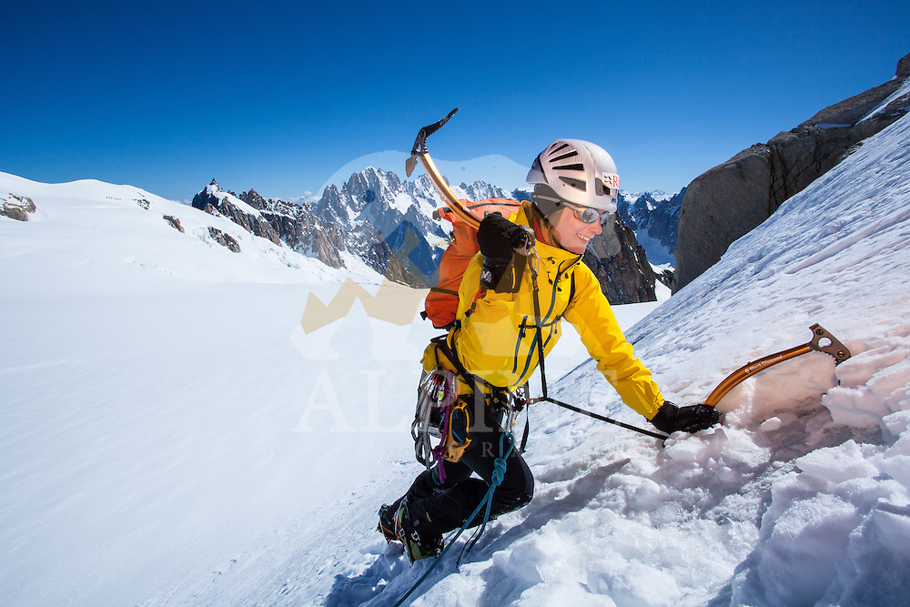 A female climber, as seen making a placement with an ice tool on a snowy slope of Pointe Lachenal on a sunny Summer afternoon in Chamonix, Mont Blanc, France.