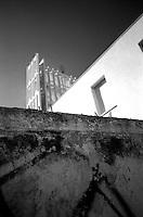 """La Concattedrale Ë stata costruita nel 1970 su progetto del famoso architetto GiÚ Ponti. Accanto al patrono di Taranto (San Cataldo) a partire dallo scampato terremoto di due secoli fa, la Vergine Ë ritenuta la protettrice della citt?. E cosÏ la Concattedrale Ë stata dedicata alla Gran Madre di Dio. Nel progetto realizzato da GiÚ Ponti, il luogo di culto doveva avere uno stretto legame con la tradizione marinara del capoluogo ionico..La facciata, infatti, rappresenta una """"vela"""" che si riflette nell'acqua delle tre vasche collocate nel piazzale antistante, e cioË il mare. In realt? la Concattedrale ha una duplice facciata..La chiesa superiore puÚ ospitare 3.000 persone. Anche l'interno ci sono dei richiami marinareschi, come le due colonne ai alti del presbiterio che reggono delle ancore simboliche. L'organo Ë nascosto all'interno della chiesa, e il suono sembra che si propaghi in maniera corale. L'altare maggiore Ë tutto di pietra, con decorazioni in ferro rozzamente colorato di verde per la parte rivolta ai fedeli..Lo stesso GiÚ Ponti dipinse sulla parete dietro all'altare l'Angelo dell'Annuncia-zione e la Madonna. Per oltre un decennio la Concattedrale Ë rimasta priva delle vasche per la sua """"vela"""", che sono state ripristinate di recente dall'Amministrazione Comunale (fonte http://wikimapia.org/1658965/Concattedrale-di-Taranto)..La fotgrafia ritrae la Concattedrale, visibile sullo sfondo, protetta da un muro sormontato da pezzi di vetro (gli offendicula, nella tradizione giuridica, sono strumenti atti a difendere la propriet?, come punte affilate dei cancelli o, appunto, pezzi di vetro sul muro.. ."""