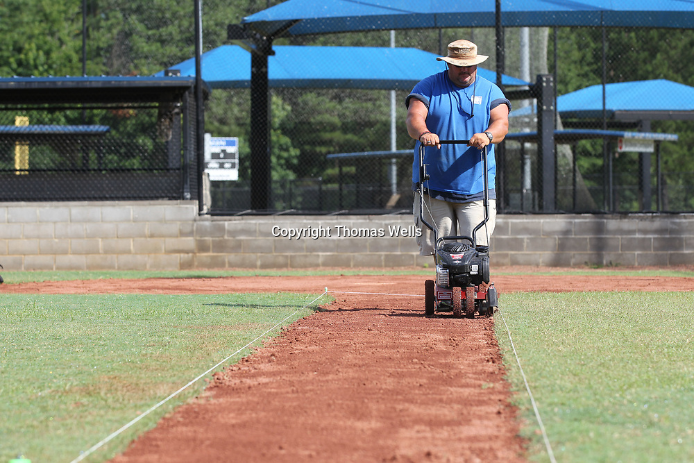 Rickey Gurley Jr. uses a edger to make a straight cut down the string along the third baseline as he and the crew get the baseball feilds at Ballard park ready for a weekend tournament.