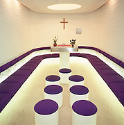 In the terminal at Charles de Gaulle/Roissy airport, Paris France, the peace of the airport chapel looks like a Star Trek-style place of worship, typical of the new airport experience pushed upon in the late '60s and early '70s. Short stools and padded benches line the intimate space in the satellite building. Designed by Paul Andreu, Charles de Gaulle became a symbol for airport modernity becoming an 'Aérogare' where trains and planes whisk the new world traveller of the late '60s, away beyond an ever-extending horizon. From here, the Air France Concorde crashed on the aviation employment town of Gonesse on July 25th 2000. Picture from the 'Plane Pictures' project, a celebration of aviation aesthetics and flying culture, 100 years after the Wright brothers first 12 seconds/120 feet powered flight at Kitty Hawk,1903.