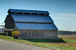 14 Sep 2006:  A large rustic frame structure barn stands near a road with some grain bins in the fall in Parke County Indiana.  The barn has a weather vane on the roof and a steel roof has replaced the original shakes.<br /> <br /> This image was produced in part utilizing High Dynamic Range (HDR) processes.  It should not be used editorially without being listed as an illustration or with a disclaimer.  It may or may not be an accurate representation of the scene as originally photographed and the finished image is the creation of the photographer.