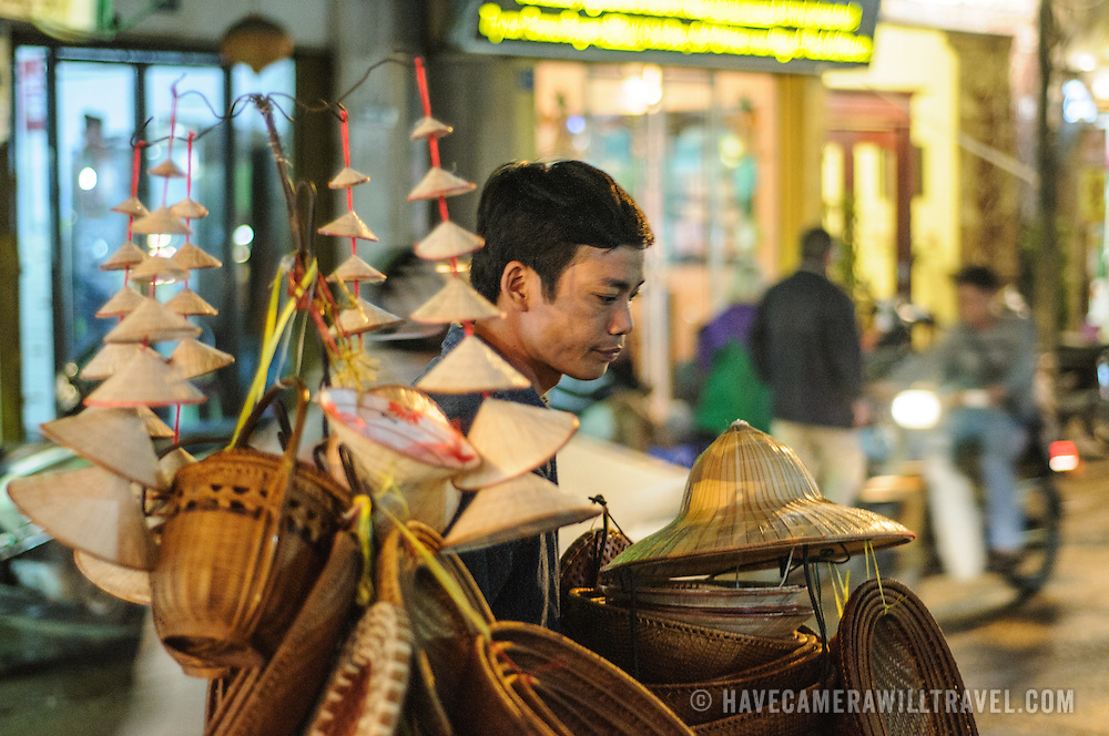 A street vendor sells Vietnamese conical hats and related souvenirs on a street in Hanoi's Old Quarter.