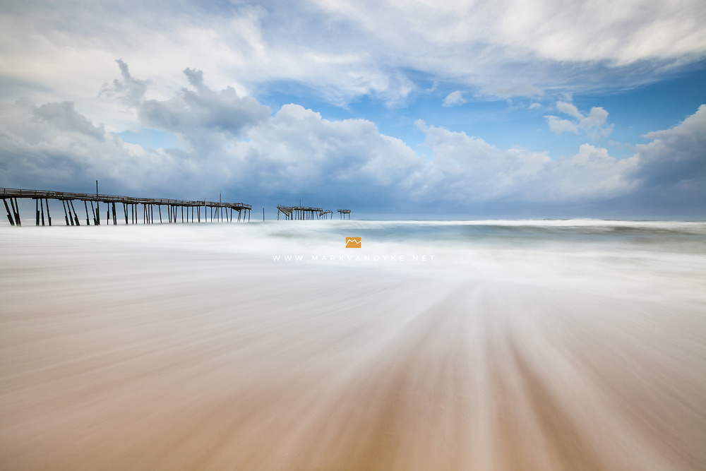 A long exposure emphasizes the push and pull of the Atlantic Ocean around the broken Frisco Fishing Pier along the Cape Hatteras National Seashore.  This iconic landmark along the Outer Banks was sold to the National Park Service in 2013 and plans are underway to remove the remainder of the standing structure.