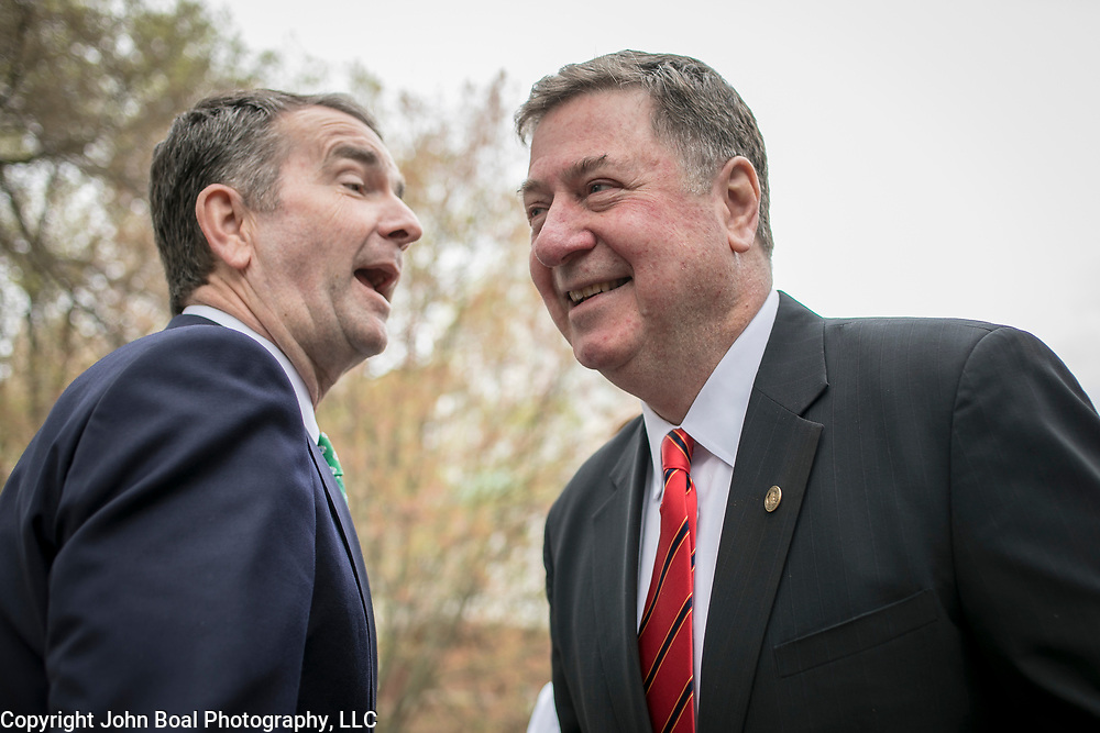 Virginia Governor Ralph Northam, left, greets former Va Gov. George Allen, during the dedication ceremony for Mantle: Virginia Indian Tribute, a monument designed on Virginia State Capitol Square, in Richmond, Virginia, on Tuesday, April 17, 2018. John Boal Photography
