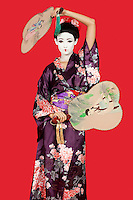 Portrait of Japanese woman in kimono holding fans standing against red background