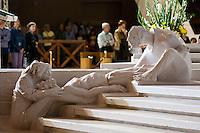 """È stata inaugurata il 1° luglio 2004, la nuova Chiesa di San Pio da Pietrelcina progettata dall'architetto Renzo Piano. Esattamente 45 anni prima, nel 1959,  veniva inaugurata la chiesa """"grande"""" di Santa Maria delle Grazie. .Sorta a fianco del santuario e convento in cui visse il frate, ha la forma di una conchiglia e la sua pianta ricorda quella della spriale archimedea. Enormi archi parto dal perimetro esterno e terminano nel fulcro della """"conchiglia"""" dove è posto l'altare. Possenti staffe d'acciaio, ancorate agli archi, sorreggono la volta che ricoperta di rame preossidato espone alla vista un intenso un colore verde-rame.   .Con i suoi 6000 mq, è la seconda chiesa più grande in Italia per dimensioni, dopo il Duomo di Milano. Può ospitare oltre 7000 persone e per la sua realizzazione sono state impiegati 30.000 metri cubi di calcestruzzo, 1.320 blocchi in pietra di Apricena, 70.000 metri cubi di scavo in roccia, 60.000 chili di acciaio, 500 mq di vetro, 19.500 mq di rame preossidato. Ogni anno è meta di oltre sei milioni di pellegrini..Nella foto il gruppo scultoreo realizzato da Giuliano Vangi e raffigurante la deposizione."""