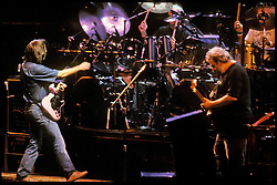 Bob Weir and Jerry Garcia with Bill Kreutzmann and Mickey Hart in background. The Grateful Dead in Concert at the Brendan Bryne Arena, East Rutherford NJ, on March 30th 1988. View front of stage at level from stage left arena.