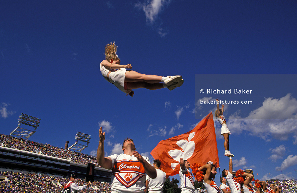 A cheerleader is thrown high into the air during a college football game between the home team Georgia Tech and visiting Clemson, at Georgia Tech University, on 5th May 1995, in Atlanta, Georgia, USA.