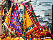 "23 JUNE 2015 - MAHACHAI, SAMUT SAKHON, THAILAND:  Prayer flags are carried through Mahachai during the City Pillar Shrine procession in Mahachai. The Chaopho Lak Mueang Procession (City Pillar Shrine Procession) is a religious festival that takes place in June in front of city hall in Mahachai. The ""Chaopho Lak Mueang"" is  placed on a fishing boat and taken across the Tha Chin River from Talat Maha Chai to Tha Chalom in the area of Wat Suwannaram and then paraded through the community before returning to the temple in Mahachai.  PHOTO BY JACK KURTZ"