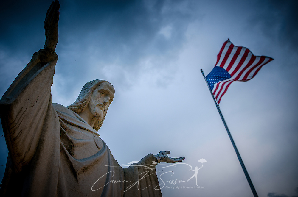 A statue of Jesus stands on the lawn of St. Margaret Catholic Church, June 16, 2013, in Bayou La Batre, Alabama. Beside it is an American flag. (Photo by Carmen K. Sisson/Cloudybright)