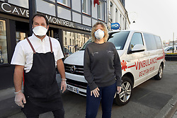 09 April 2020. Montreuil Sur Mer, Pas de Calais, France.<br /> The 'Vinbulance.' The 4th emergency service delivering wine, beer and spirits in and around Le Touquet and Montreuil Sur Mer in Hauts de France, 1 hour south of Calais.<br /> Olivier and Belinda Tirel, (both 45 yrs old) owners of La Cave de Montreuil and Le Touquet with their emergency vehicle, the 'Vinbulance.' <br /> <br /> Belinda, an Australian met Olivier, a Frenchman in England when they both worked at Café Rouge in Kew Gardens in London in 1996. Married 24 years with 4  children they own 2 wine shops, one in Le Touquet (since 2007) and one in Montreuil Sur Mer (since 2015). <br /> <br /> Belinda came up with the idea of the 'Vinbulance' having seen a photo of a 'winebulance' on the internet. Olivier and Belinda contacted friends who are doctors, nurses and medical technicians before embarking on the idea. They wanted to check that their idea would not be offensive to those working on the front lines against coronavirus. All their friends in the medical profession thought it would be an excellent idea to try and cheer people up, bring a smile to their faces and help lift people's spirits in these difficult times. 'Which was the point of it,' explained Olivier.<br /> <br /> 'People give us thumbs up, toot their horns and wave when they see the 'vinbulance.' Belinda was stopped twice in the past 2 days with people asking to take photos of her and the 'vinbulance' explained Olivier. 'One person, a regular customer even ordered some wine because he did not know we were open.'<br /> <br /> 'The coronavirus crisis has badly affected business. We have lost all of our restaurant trade and people just are not having parties and celebrating as they were before all this,' explained Olivier.<br /> <br /> 'We are considered a business of 'première nécessité,' (first necessity) as declared by the  French Government which means we can remain open. We don't get any help from the government financially, we have 4 c