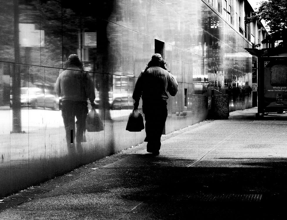 A man walking along a street carrying a bag