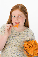 Overweight girl eating potato chips