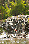 Man enjoying shower of hot water at Sunflower hot springs on the Middle Fork of the Salmon River, Idaho.