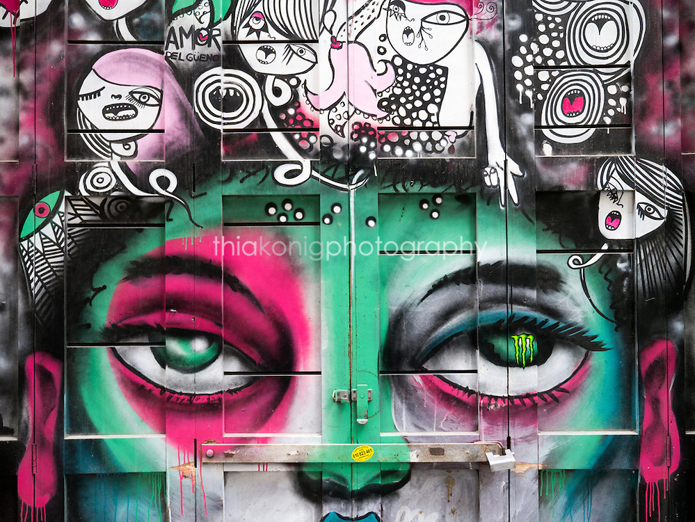 A colorful graffiti mural with cartoon characters for hair and big green eyes, Barcelona, Spain.