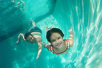 Father and daughter swimming, underwater view