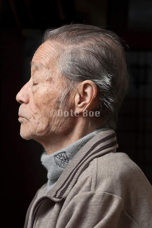 side view portrait of elderly Japanese man with eyes closed