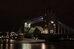 © Licensed to London News Pictures. 05/07/2014. London, UK. Tower Bridge in London is seen with lights switched off as the bridge lifts for a passing boat. Landmarks across London and the UK are turning their lights off from 10pm to 11pm tonight to mark the First World War centenary. Photo credit : Vickie Flores/LNP