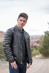 man in leather jacket on a dirt road