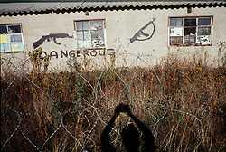 1993 - Thokoza, South Africa - A migrant workers hostel with guns and the word 'Dangerous' painted on the building.  Inkatha Freedom Party hostel residents controlled the hostels around Johannesburg. Thousands of people, both civilians and combatants died in the so-called Hostel War from 1989-1995..(Credit Image: © Greg Marinovich/ZUMA Wire/ZUMAPRESS.com)