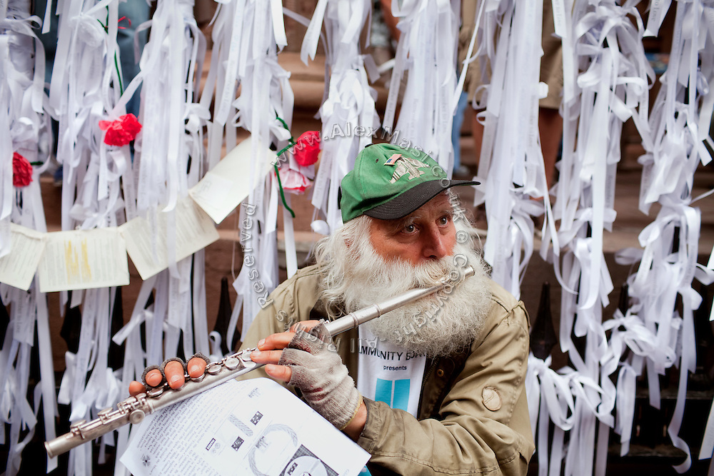 An old man distributing flyers about a personal alternative creed and theory about life, is playing the flute on the street in Lower Manhattan, New York, USA, on the 10th anniversary of the 9/11 attacks on the Word Trade Centre.