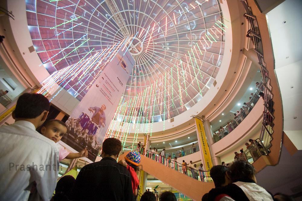 A family looks at a promotional event held inside the Inorbit Mall Malad, in Mumbai, on Sunday Dec. 28, 2008.  Photographer:Prashanth Vishwanathan