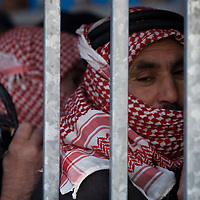 Palestinian workers queue along the separation wall at the checkpoint 300, the crossing passage between Bethleem and Jerusalem, on December 15. 2010 in Bethleem. Workers arrived every day at two o'clock in the morning  to catch a place at the entrance of the checkpoint, so they can arrived at time to their work in the Israeli side. Photo by Olivier Fitoussi