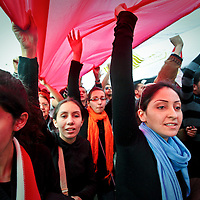 A group of women carry an Egyptian flag through Tahrir Square during anti-government protests in Cairo, Egypt. February 2011.