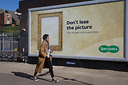 A lady walks past a large billboard ad for high street opticians chain, Specsavers, on 2nd October 2019, in London, England.