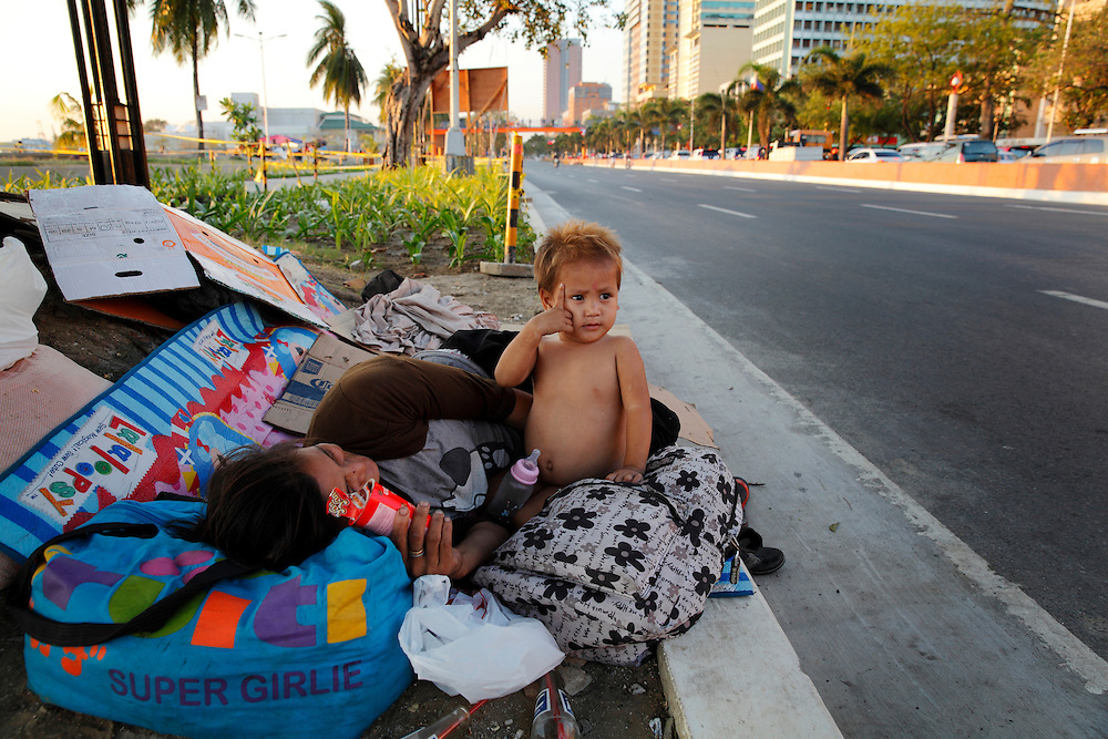 Philippines, Manilla, Roxas boulevard. Homeless baby and grandmother rest by the side of the road as traffic passes by.<br /> <br /> Photo: &copy; ZuteLightfoot