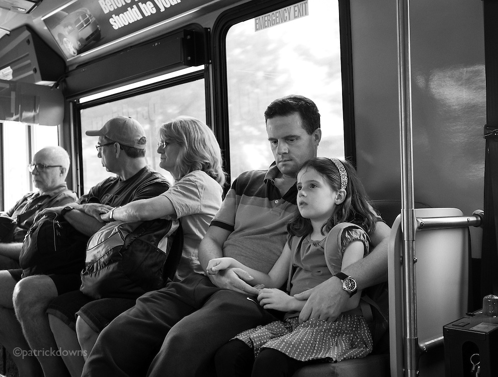 A travel-weary dad and daughter on the last leg home from a long trip, at SeaTac airport on the parking lot bus.