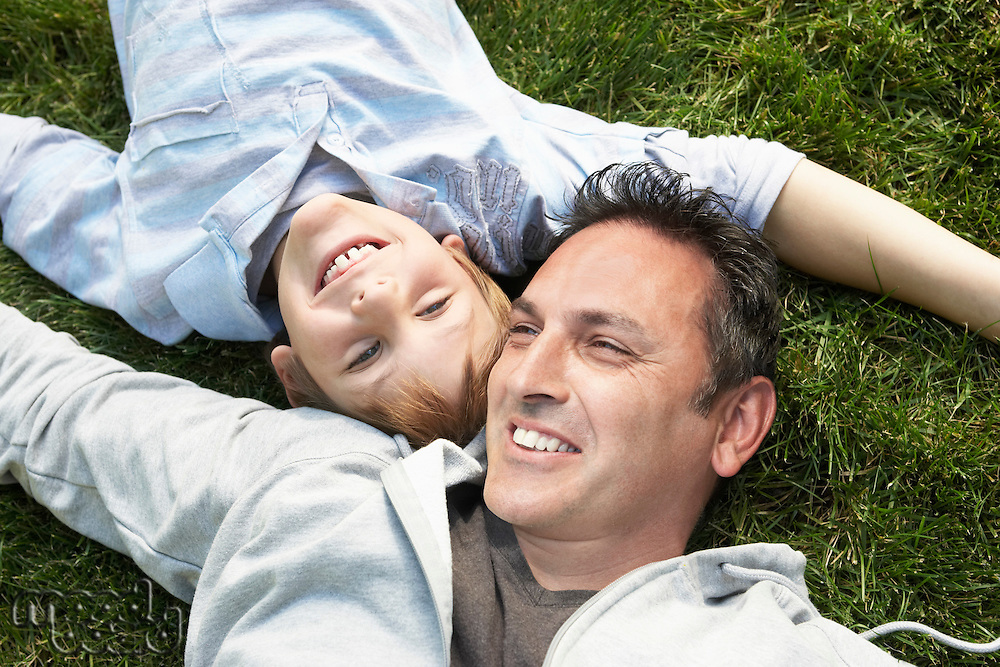 Father and son lying on grass view from above