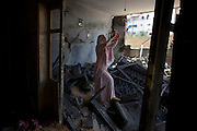 Palestinian Hadil Amar,21,uses her tablet to photograph herself with the damages to her family's home in Tel al Hawa in central Gaza August 11,2014 . The family fled their home late last night just before the cease fire after it was hit with a warning rocket by a Israeli drone just before it was targeted by Israeli war jets . Witnesses claim the home was hit twice .