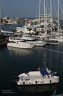 Official America's Cup boat passes superyacht marina at center of Port America's Cup; Valencia, Spain.