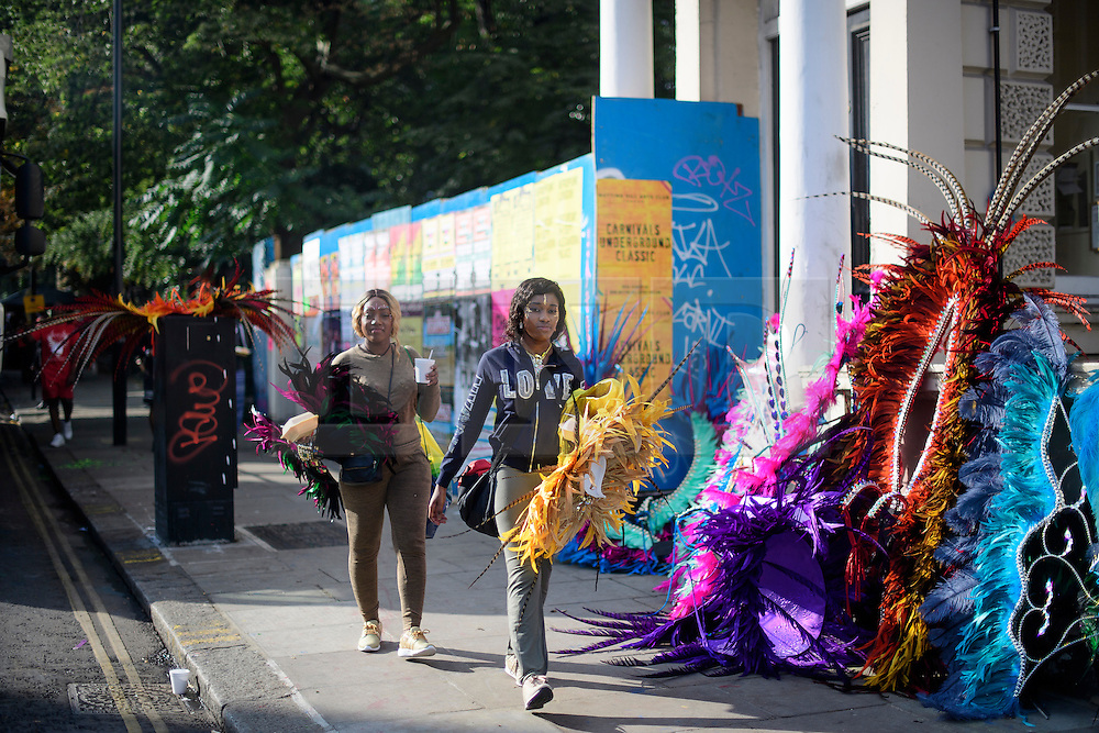 © Licensed to London News Pictures. 29/08/2016. London, UK. A carnival goers walk along Ladbroke Grove before taking part in day two of the Notting Hill carnival, the second largest street festival in the world after the Rio Carnival in Brazil, attracting over 1 million people to the streets of West London.  Photo credit: Ben Cawthra/LNP