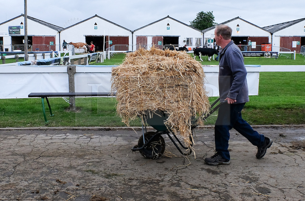 © Licensed to London News Pictures.14/07/15<br /> Harrogate, UK. <br /> <br /> A man wheels straw to the stables on the opening day of the Great Yorkshire Show.  <br /> <br /> England's premier agricultural show opened it's gates today for the start of three days of showcasing the best in British farming and the countryside.<br /> <br /> The event, which attracts over 130,000 visitors each year displays the cream of the country's livestock and offers numerous displays and events giving the chance for visitors to see many different countryside activities.<br /> <br /> Photo credit : Ian Forsyth/LNP