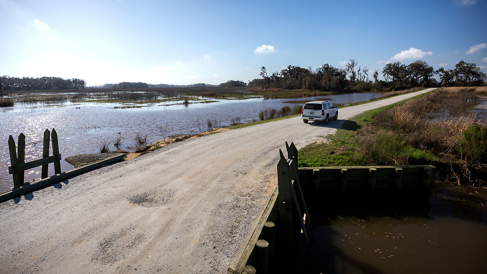 BLUFFTON, S.C. - FEBRUARY 20, 2018:<br /> Rick Kanaski, Regional Archaeologist &amp; Regional Historic Preservation Officer for the U.S. Fish and Wildlife Service drives past a levee gate used to divert fresh water into the Savannah National Wildlife Refuge. (WABE Photo/Stephen B. Morton)