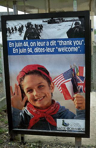 """April 1994, France --- A bus stop poster in Normandy, France, welcomes returning veterans for the 50th anniversary of D-Day and the Allies' landing sites of WW II. A caption over a happy child reads: """"On June '44, we said """"Thank you."""" On June '94, we say """"Welcome."""" --- Image by © Owen Franken/Corbis"""