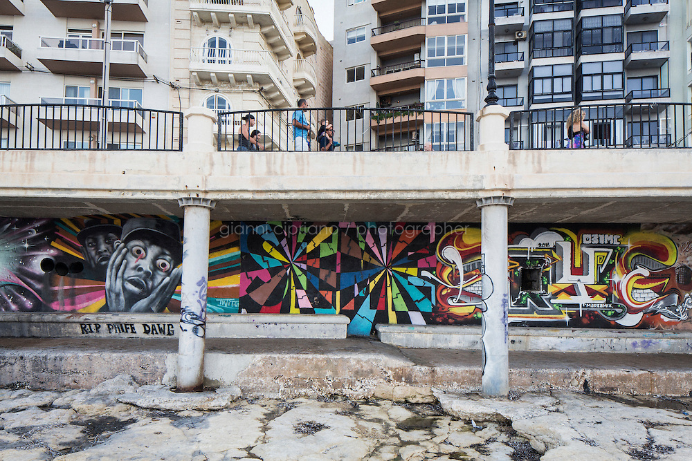 SLIEMA, MALTA - 28 AUGUST 2016: Graffitis are seen here under a overhanging footpath along the coast in Sliema, Malta, on August 28th 2016.<br /> <br /> While many cities across the world denounce the defacing of a public property, on the Mediterranean island of Malta it is encouraged.<br /> <br /> According to Sandra Borg of Arts Council Malta, street art projects &ldquo;engage with numerous communities and contribute directly to urban regeneration&rdquo;. Funding from Arts Council Malta, allows schools to offer additional creative arts subjects and many choose street art; with &lsquo;NO WAR&rsquo; creator, James Grimaud, teaching students sketching, stencil making and aerosol use.