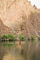 Kayaker navigates the Colorado River in his handmade wooden boat through The Black Canyon, Nevada.