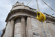A coil of electrical wiring cables is next to the walls of the Bank of England on Threadneedle Street - part of ongoing alterations to the highway during the Coronavirus pandemic in the City of London, the capital's financial district, on 6th August 2020, in London, England. SRL are the UK's only manufacturer to sell and hire traffic light equipment and their Urban64 product is the first, and only, permanent technology system to be designed uniquely for temporary installations in the U.K. The Urban64 design allows for simple and quick over-head installation, with the ability to replicate the technology provided by the preceding permanent system, and therefore maintaining traffic flow efficiency.