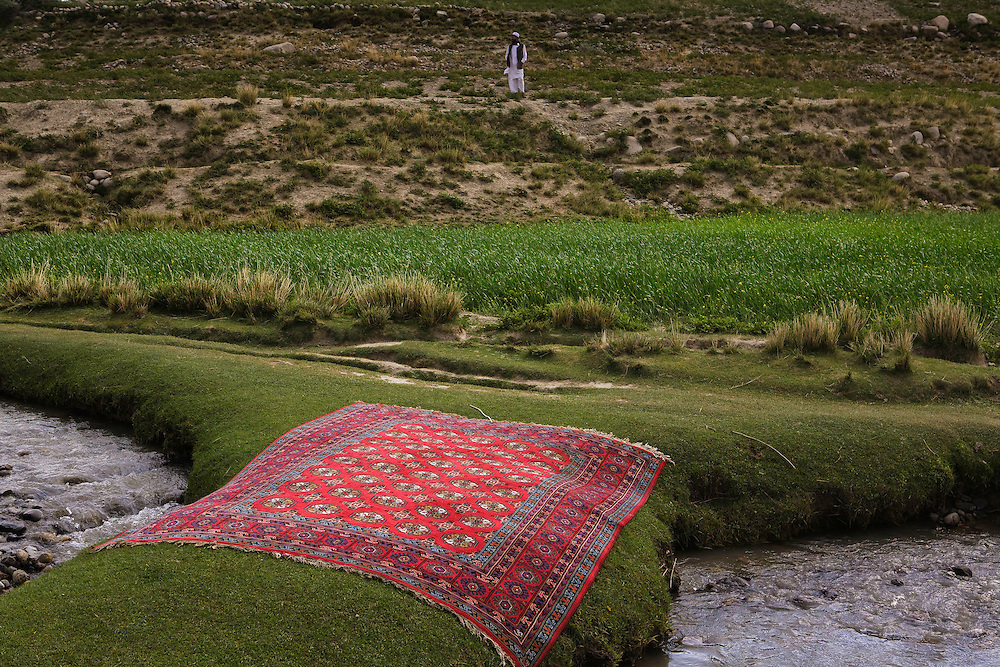 large afghan rug dries in sun after being washed in stream in nortther city of Ishkashim in Badakshan province
